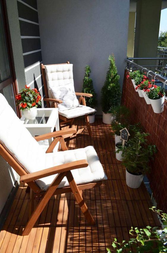 Varanda com deck de madeira, parede de tijolinhos, banco de madeira com estofado branco, mesinha de canto branca e vasos de plantas espalhados pela varanda.