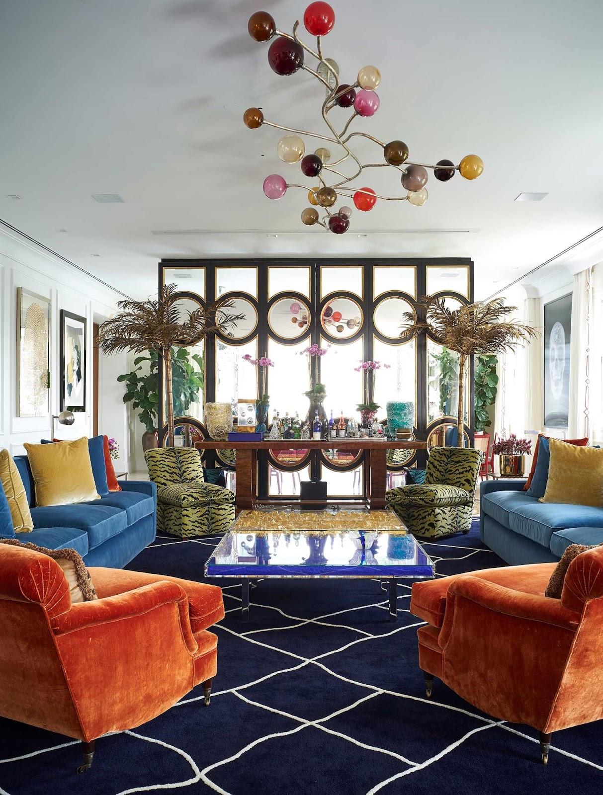 Ambiente com sofá azul, poltronas laranja e com estampa de onça, tapete azul.
