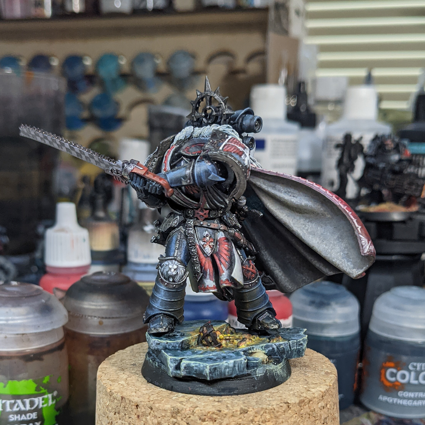A partially painted (and headless) model of a model warrior in ornate black armour.  The model is painted black, with a white and red cloak.