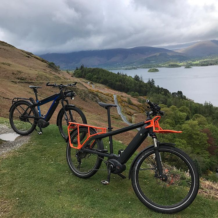 a couple of e-bikes parked in the middle of the countryside with the owners getting lots of exercise