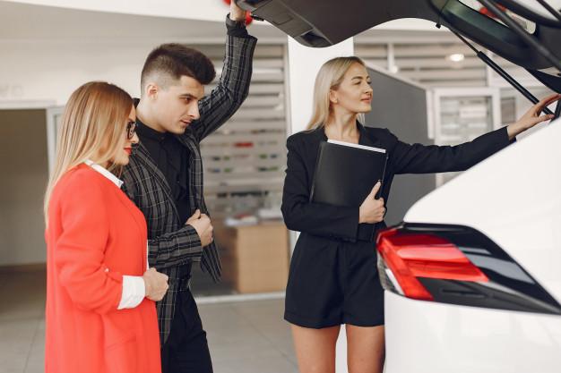Clientes analisando um automóvel que a vendedora os mostra.