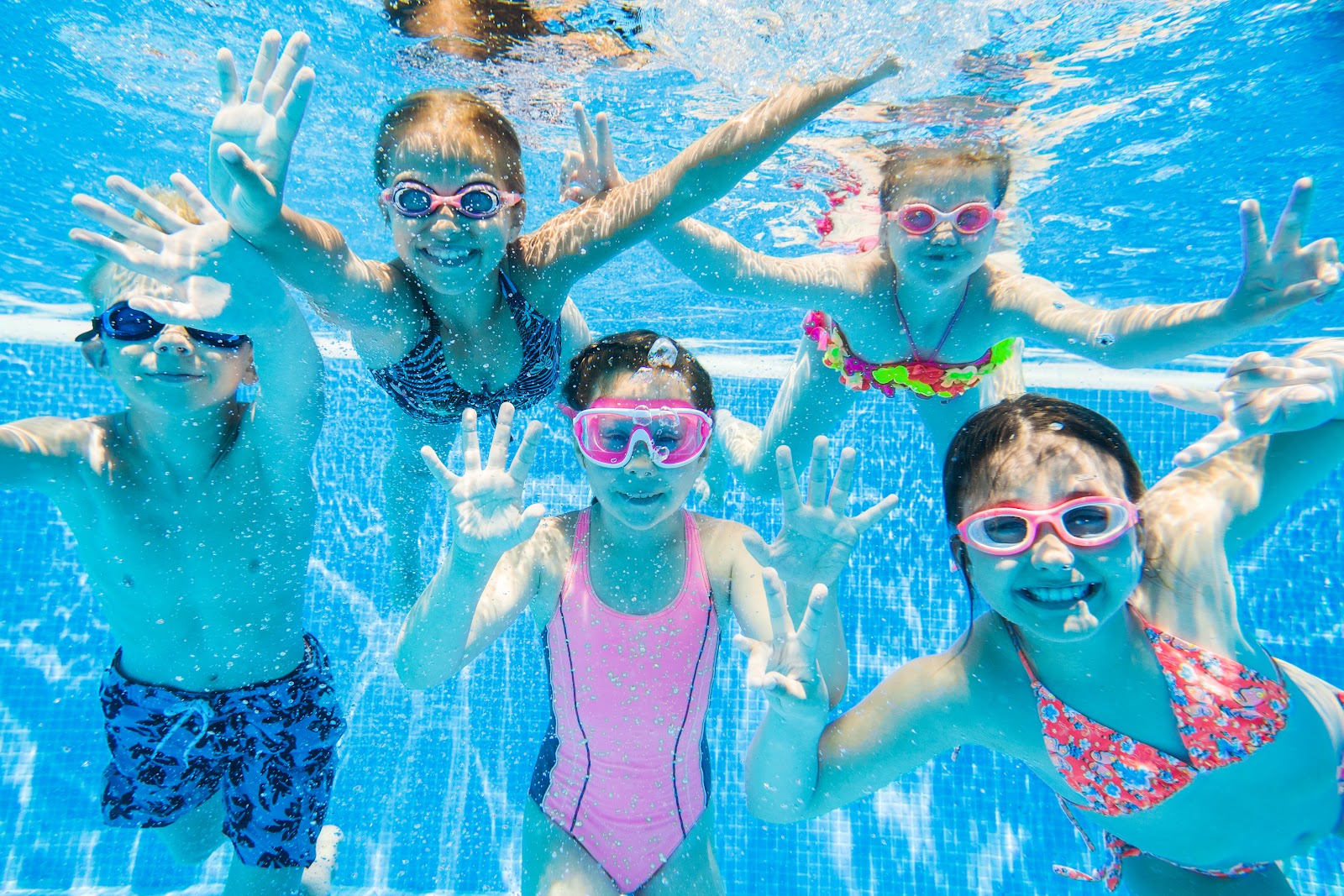 5 kids underwater in a swimming pool wearing goggles and smiling