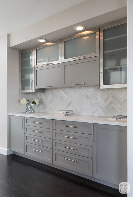 light grey shaker cabinets with matching grey walls herringbone backsplash silver pulls dark wood floors
