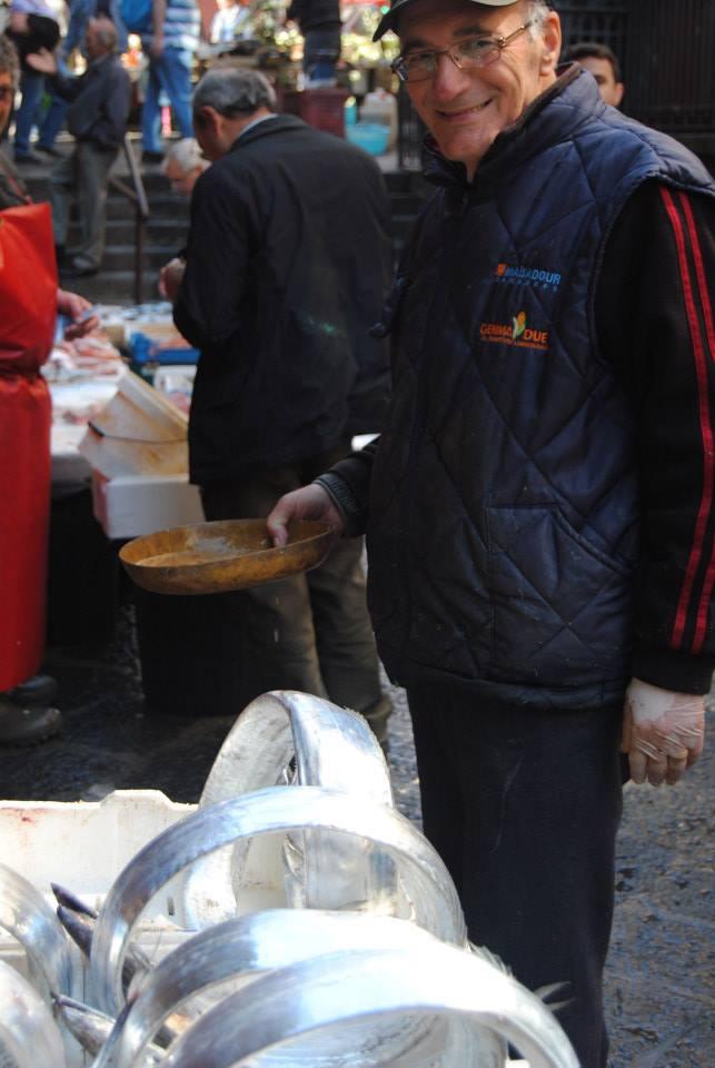 A fishmonger smiles behind his long silver fish coiled up into circles at the Catania Fish Market.