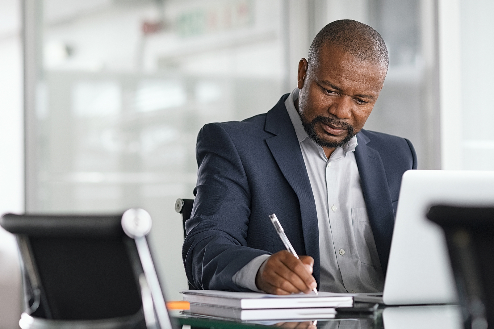 Black business professional man taking notes on a note pad with an open laptop in front of him.