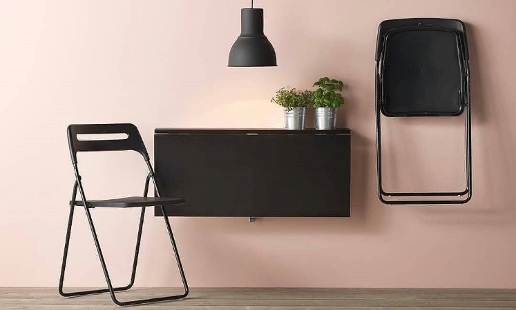a wall-mounted table and folding chairs save space in a small apartment