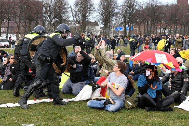Police clash with demonstrators during a protest against coronavirus restrictions in The Hague [Piroschka Van De Wouw/Reuters]