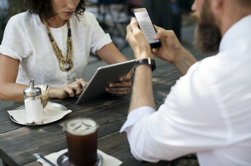 Couple at a table using a smart phone and iPad