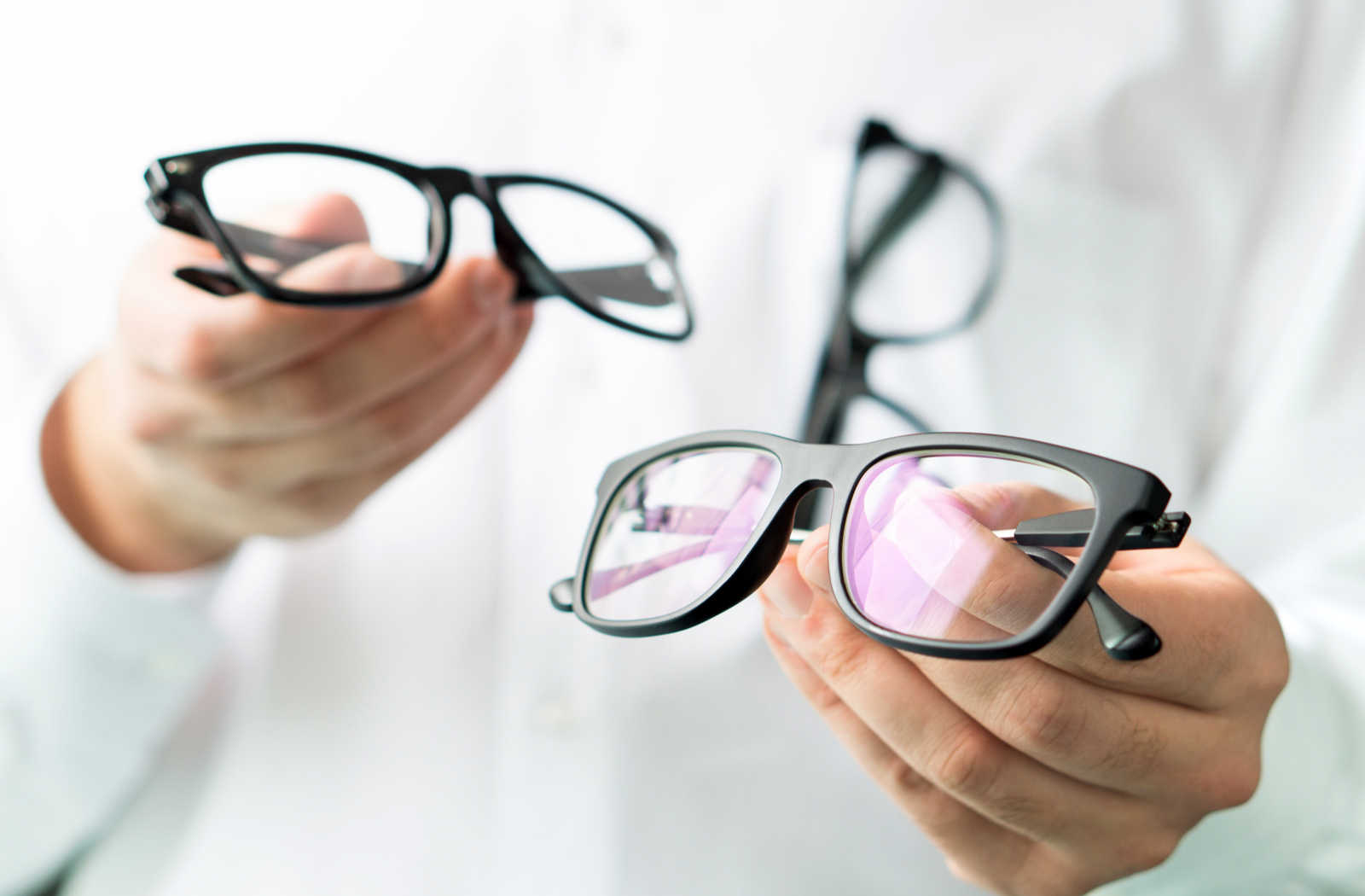 Optometrist holding 2 pairs of glasses to show the difference in lens powers