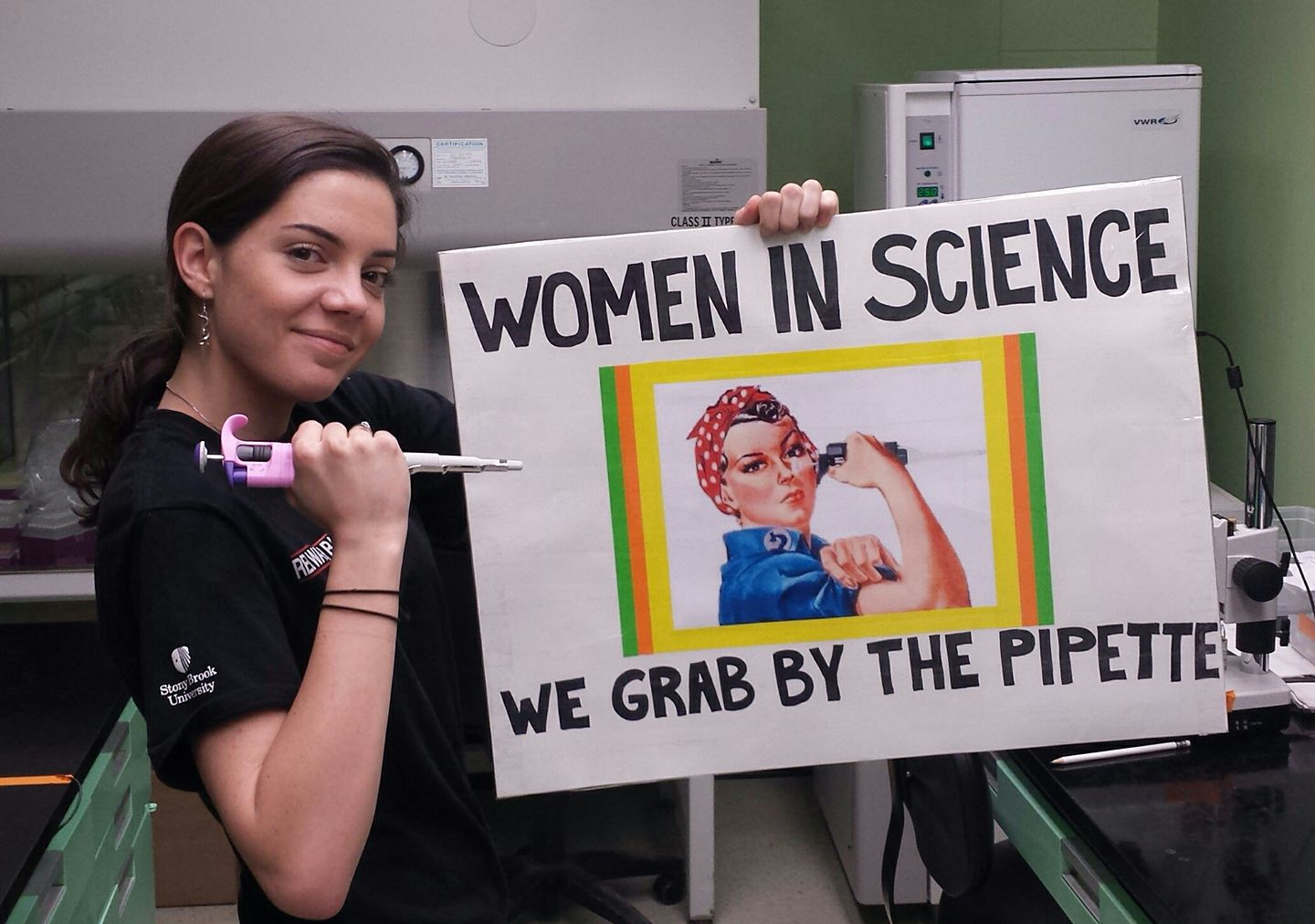 "Taylor with a sign that shows Rosie the Riveter holding a pipette, with the words ""Women in Science, we grab by the pipette"" surrounding it."