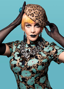 Image description: Kate O'Donnell is posed against a turquoise background. She is wearing a turquoise, black, and gold top, with long sheer black gloves. Her hair is in a short, dyed blonde bob, and she is wearing a leopard-print hat and black make-up.