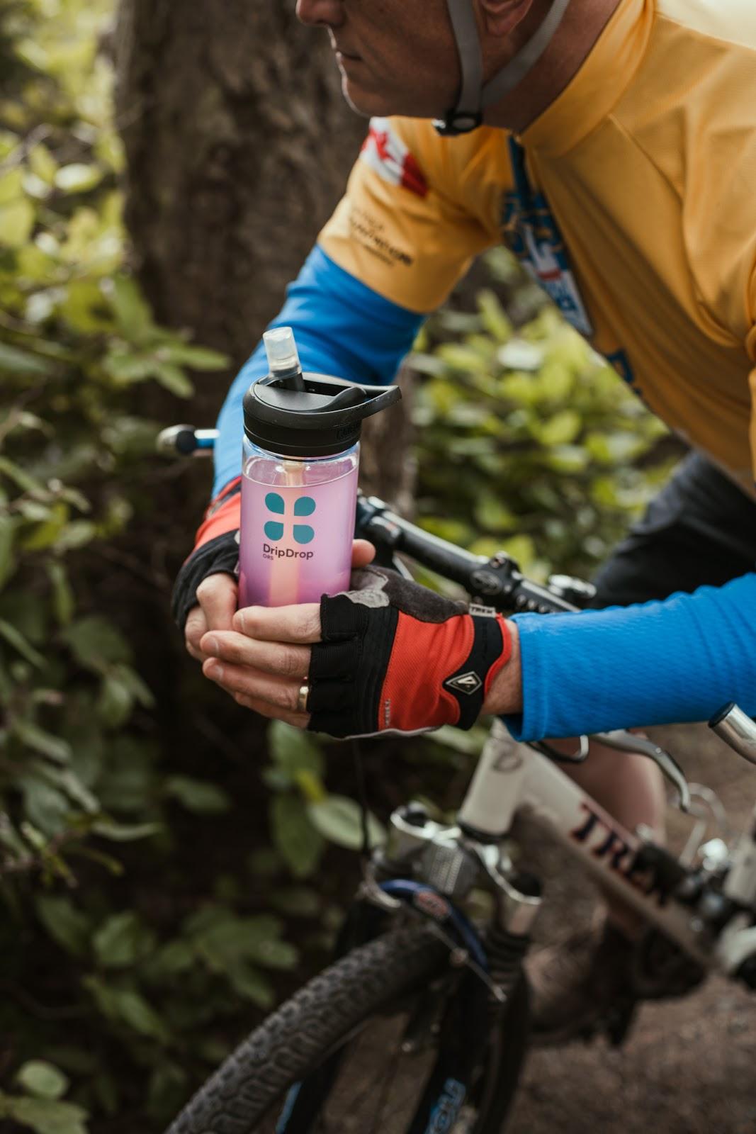 Cyclist holding a DripDrop ORS tumbler