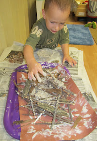 Children try to build a nest using potter's clay, leaves and sticks.