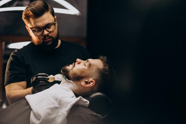 Handsome man cutting beard at a barber salon