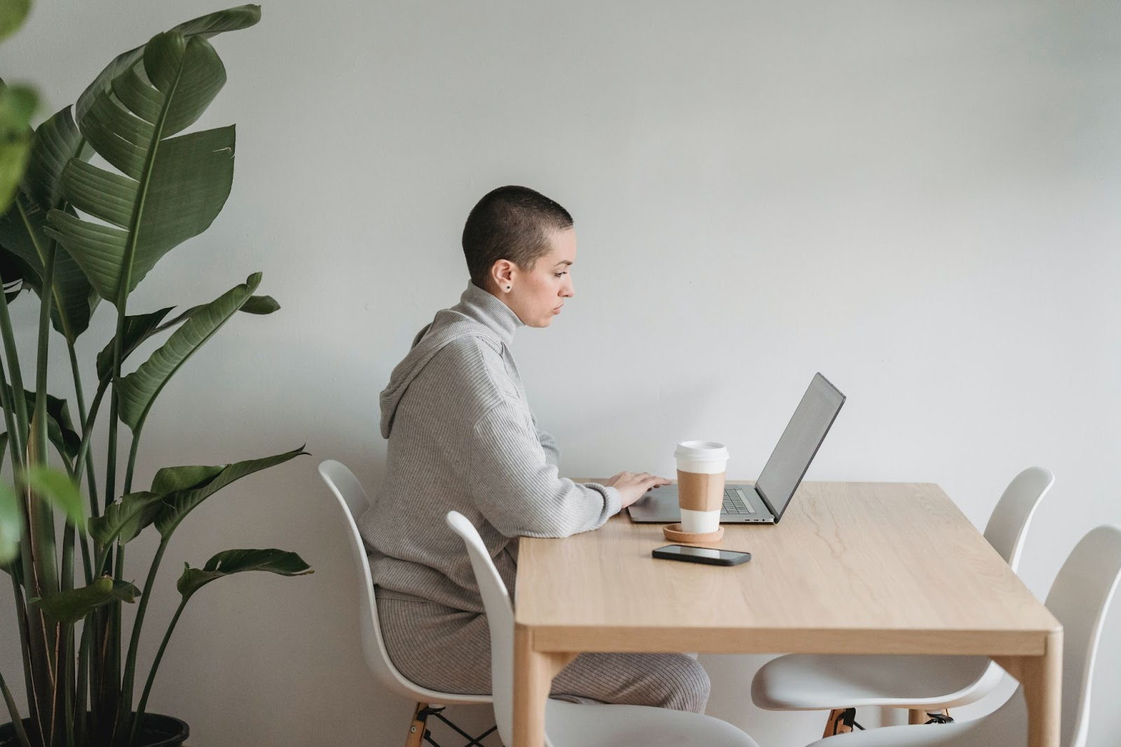 A light-skinned woman with shaved head sitting at a desk and working on her laptop. She's surrounded by leafy green house plants, and looks deeply focused.
