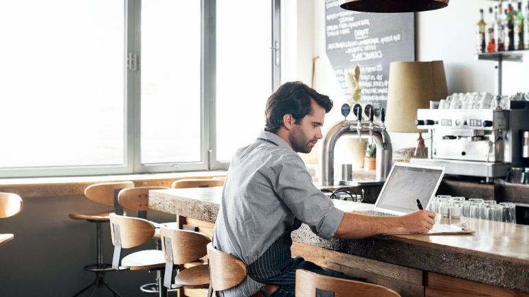 Restaurateur working on macbook at bar, crafting a misson statement.