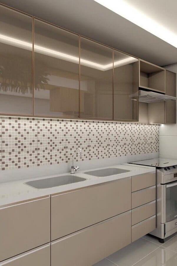 Cozinha com cores neutras, armário nude e amadeirado, pia branca e pastilhas de duas cores neutras fazendo degradê.
