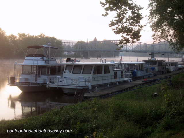 Houseboats tied off together and sharing the public docks in Malta, Oh. along the Muskingum River