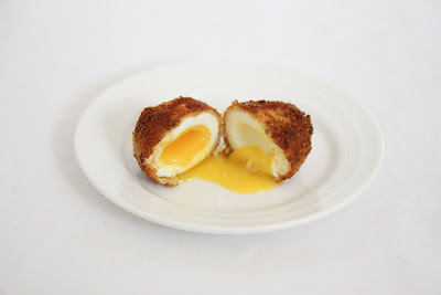 photo of two halves of a fried bacon egg on a plate