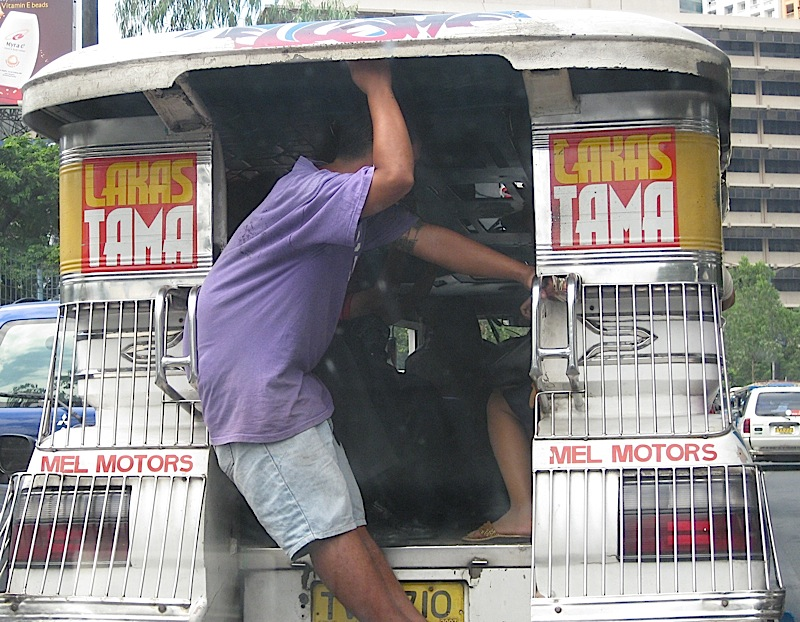 man hanging on to the outside of a jeepney