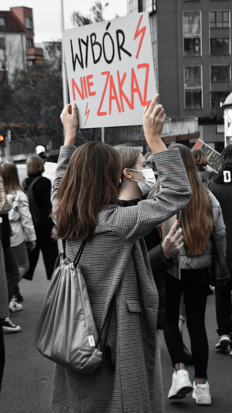 Woman holding a sign at a protest, wearing a dark jacket.