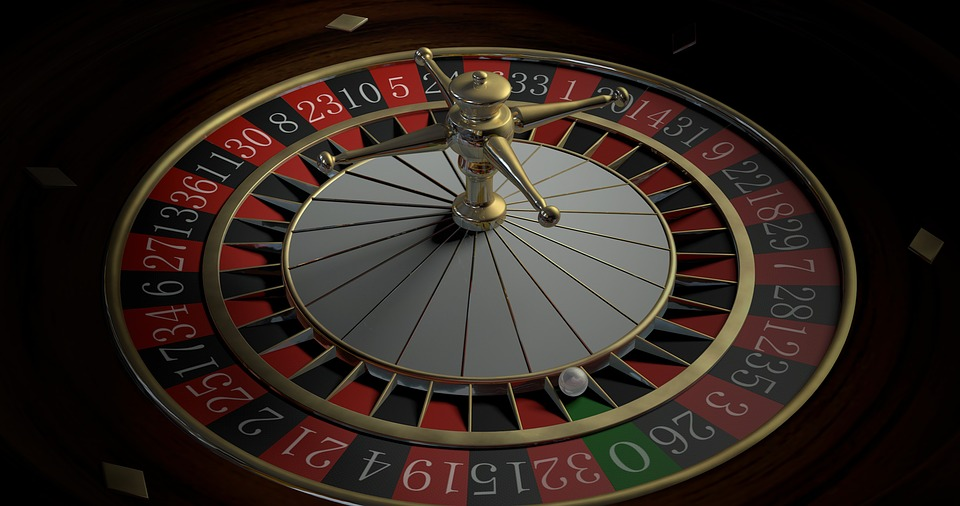 A casino roulette wheel with the white ball sitting in the green 0 section