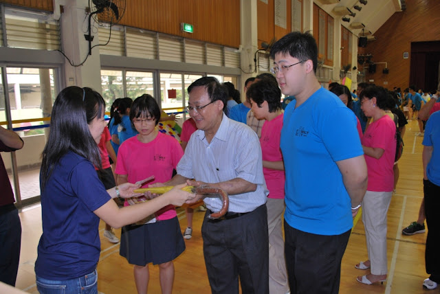 Alumni Office teacher Ms Ng Erin (left) handing over the AJCAA umbrella to AJCAA Patron Mr Seng Han Thong (centre), who is accompanied by AJCAA President Mr Lau Kiat Meng (right)