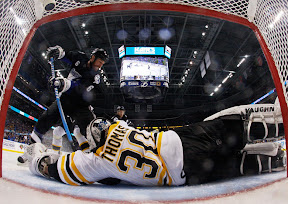 Bruins Tim Thomas make a save against Lightning's Ryan Malone