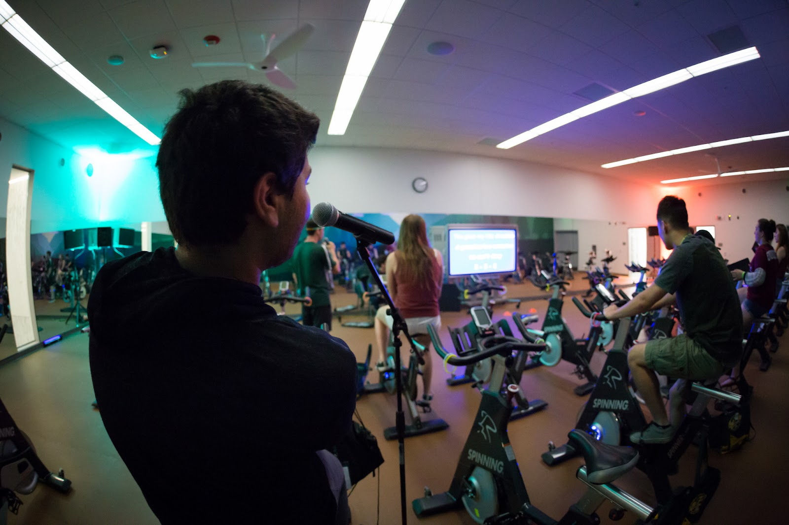A student featured singing on a microphone while other students are spinning on spin bikes at the BRIC.
