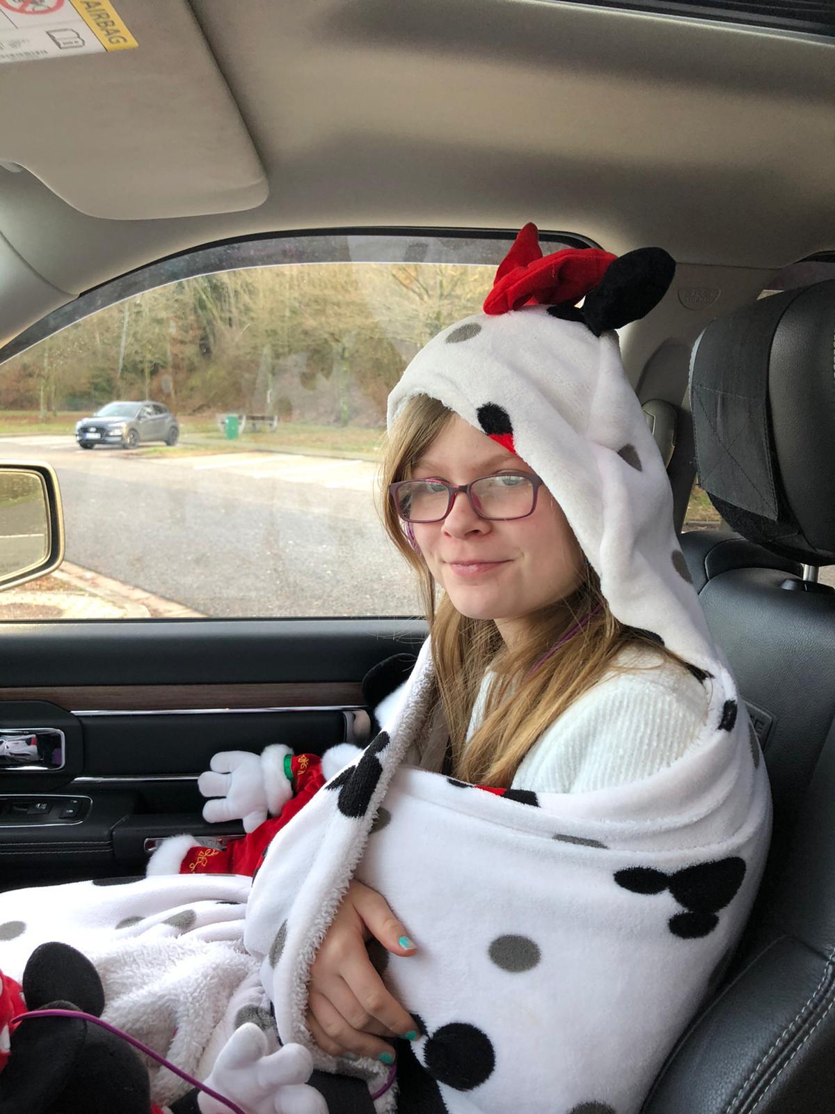 Kind sitzt in Kuscheldecke eingeholt im Auto