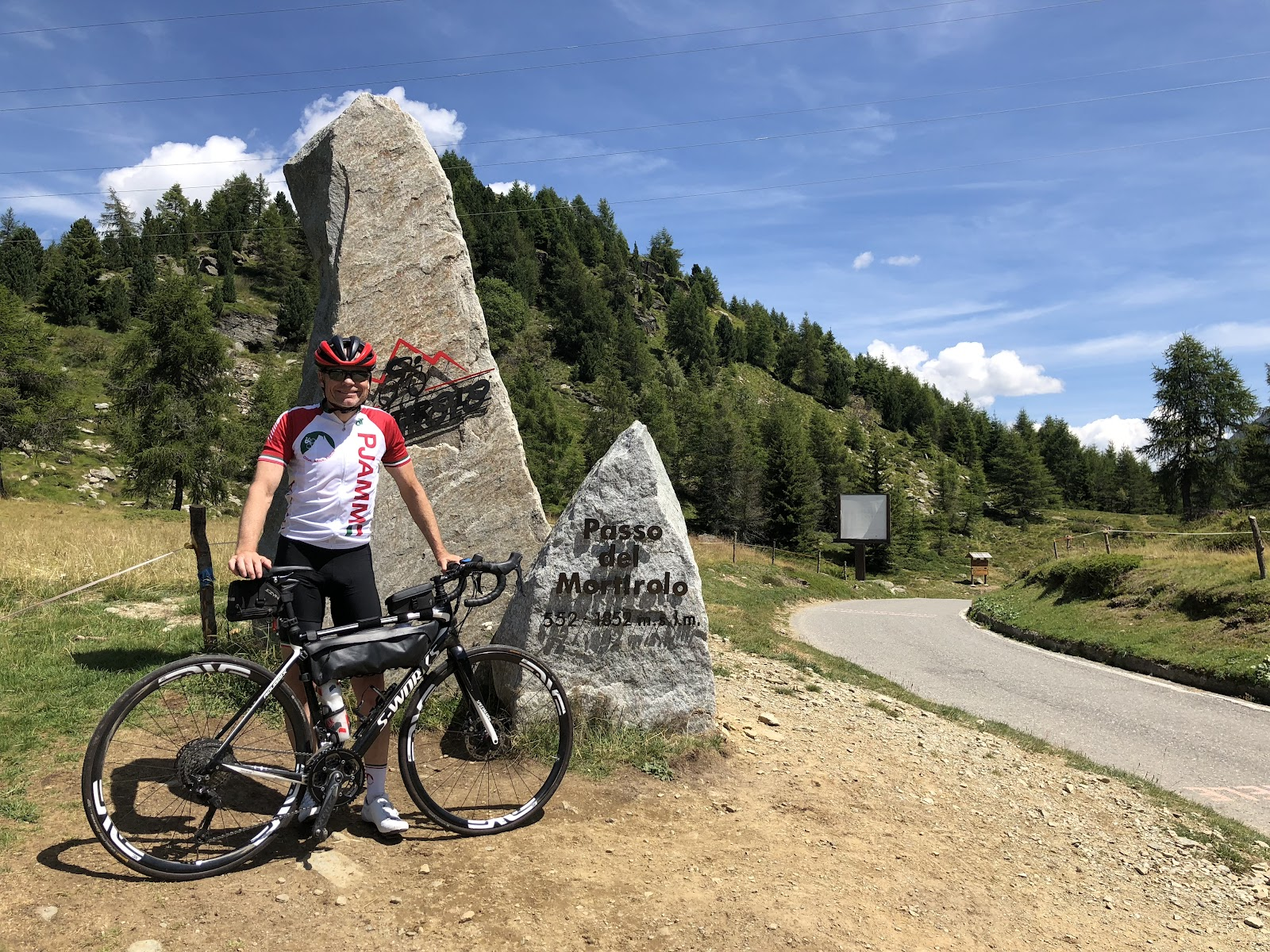 Bicycle ride of Passo del Mortirolo from Mazzo di Valtellina - John Johnson PJAMM Cycling at the pass sign