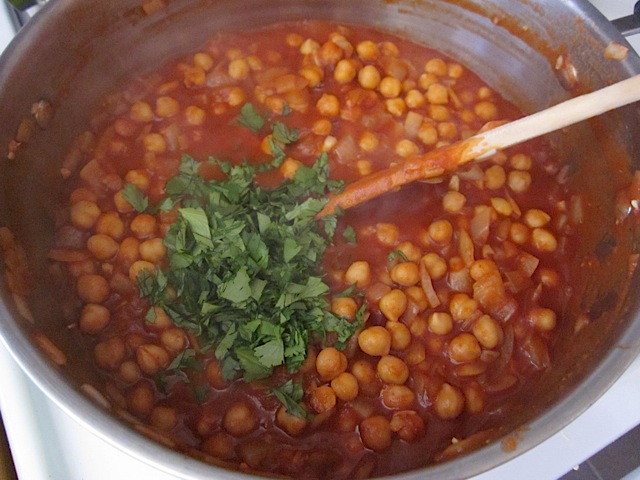 chopped cilantro added to pot of chick peas