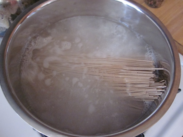 soba noodles added to boiling water in pot