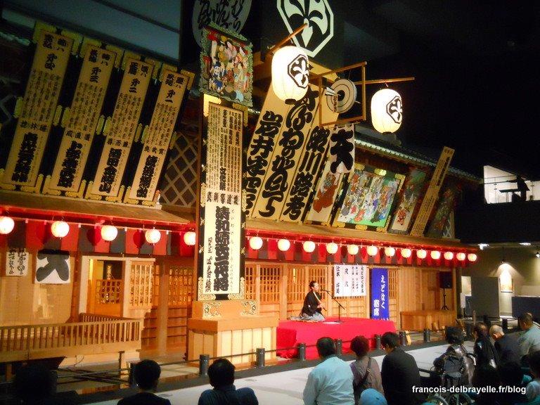 Une musicienne joue du shakuhachi devant le théâtre reconstitué