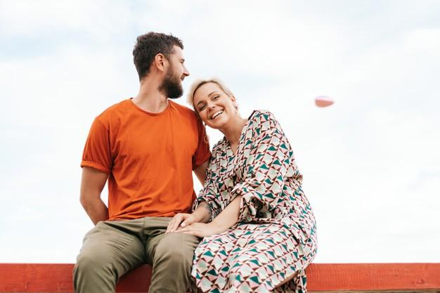 Man and woman sitting happy on a wood plank looking to a flying pink heart balloon in the sky Free Photo