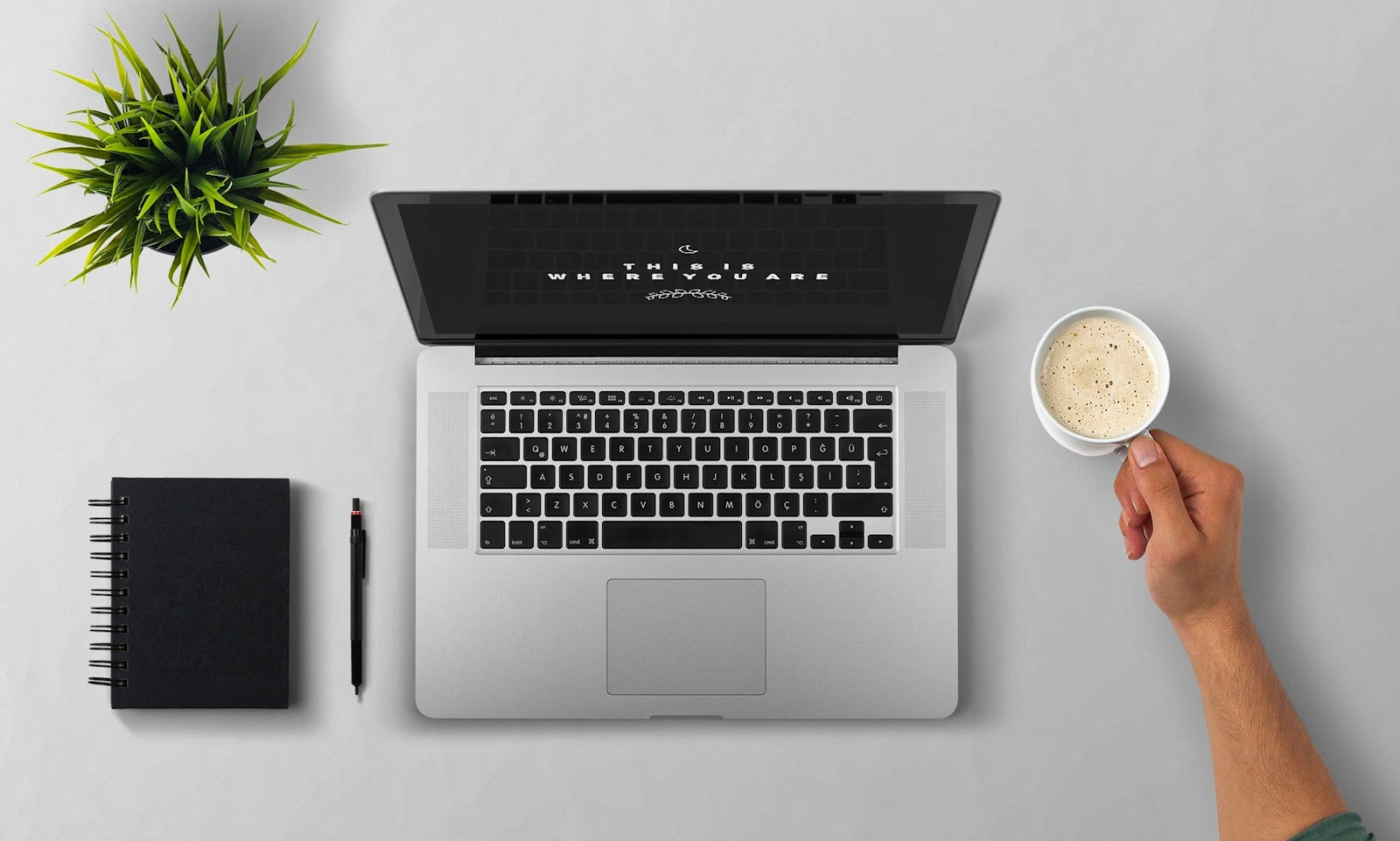 a silver laptop next to a person's hand holding a coffee and a black notebook and pen.
