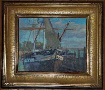This is a photo of an oil painting of a sailboat at the dock framed in gold.