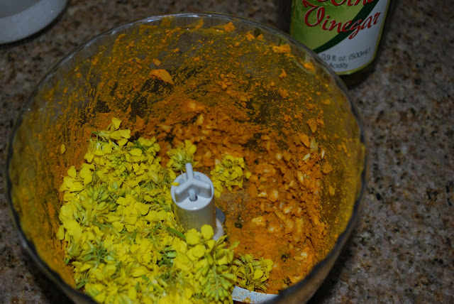 This is a photo of mustard flowers in a food processor with spices.