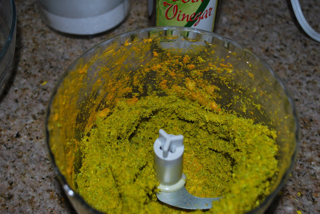 This is an image of a food processor with ground spices and mustard flowers in it.