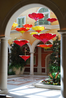 This is a photo of hand painted umbrellas as viewed through an archway into a garden.