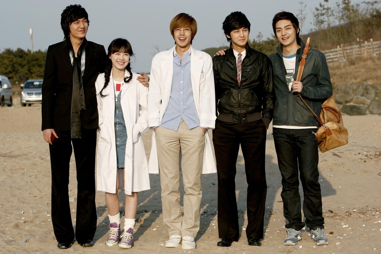 Os personagens principais posam de frente para a câmera sorrindo localizados na areia da praia