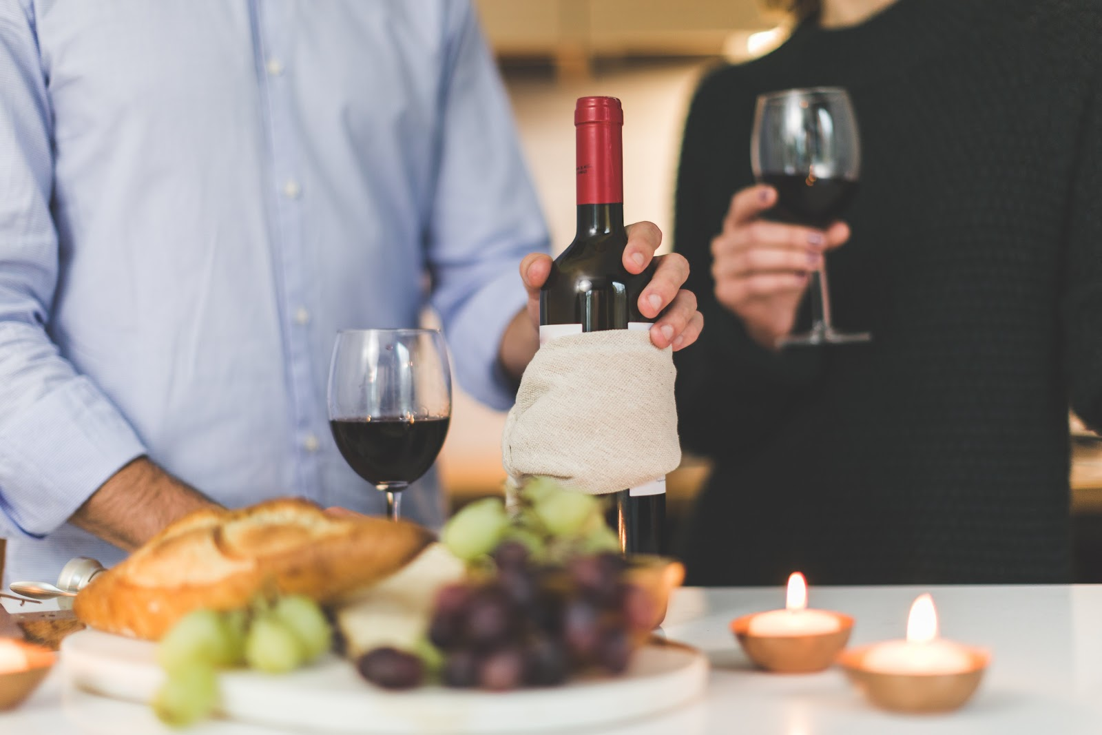 Red wine glass and wine bottle with a cheese platter; wine guide