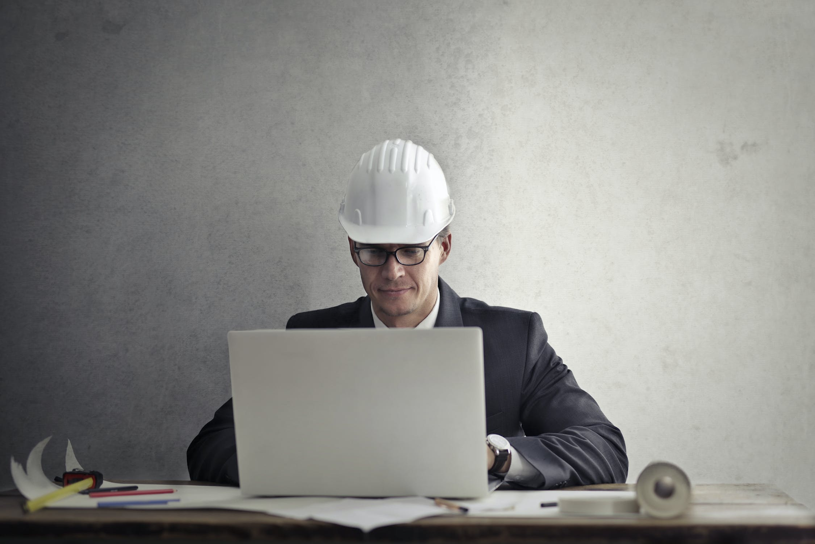 Man with white hard hat working on a laptop