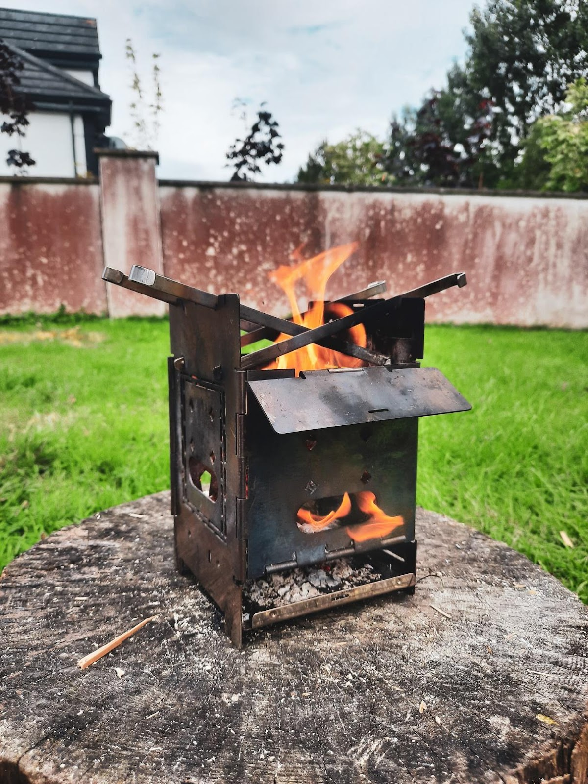 A close up of a fire place sitting in a yard  Description automatically generated