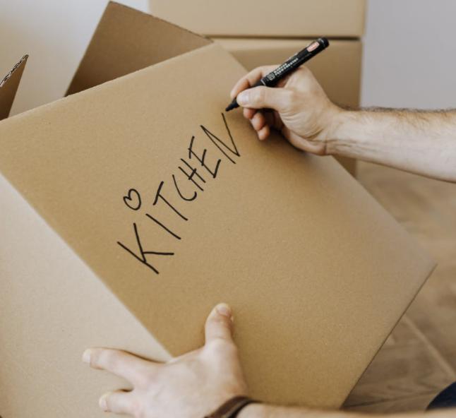 """man writing """"kitchen"""" on box"""