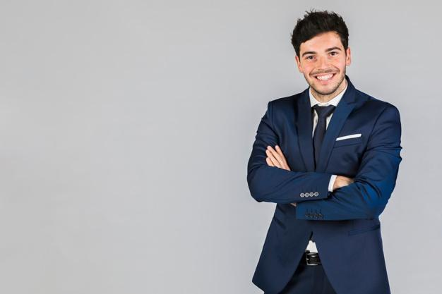 Portrait of a confident young businessman with his arm crossed standing against grey background