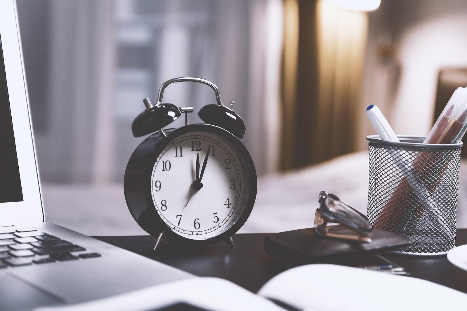 Alarm clock beside laptop for study breaks