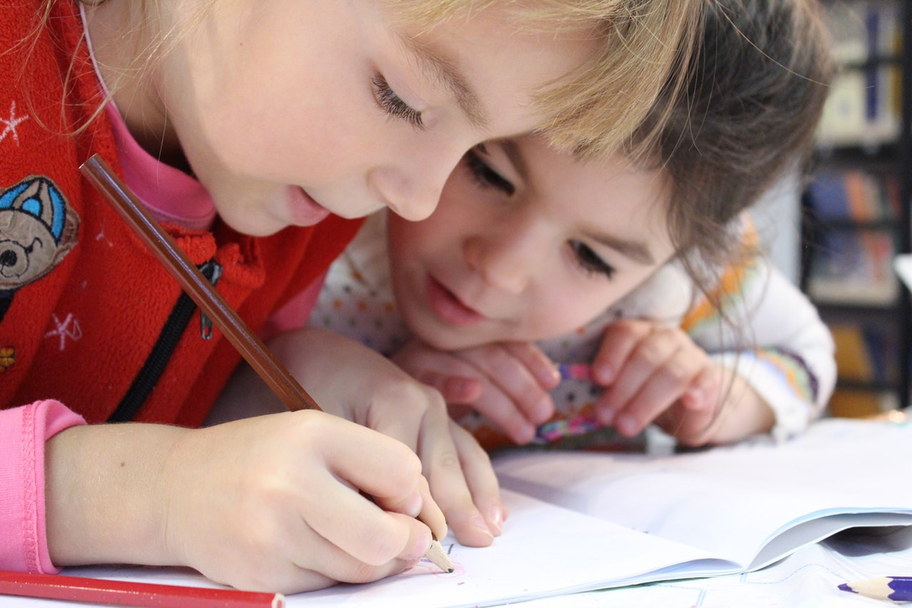 Two little girls lean over a piece of paper, working together as one of them writes.