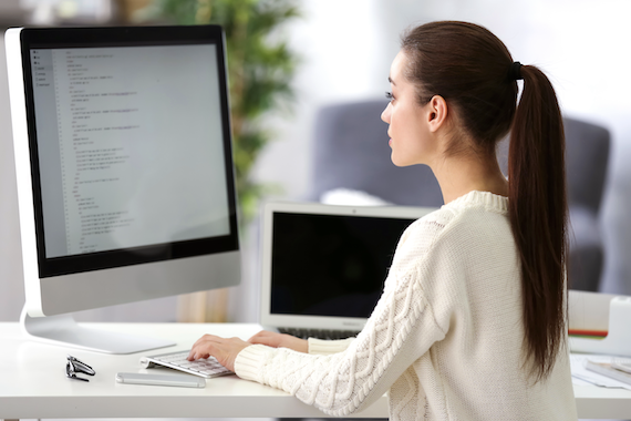 Web application development: Woman types lines of code