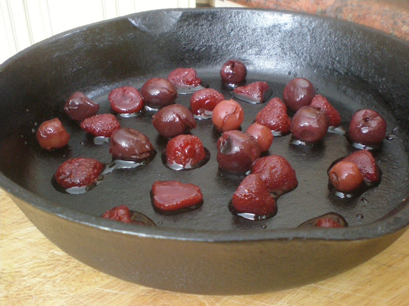 Preserved cherries and strawberries in a 10.25 inch cast iron skillet ready to receive the batter